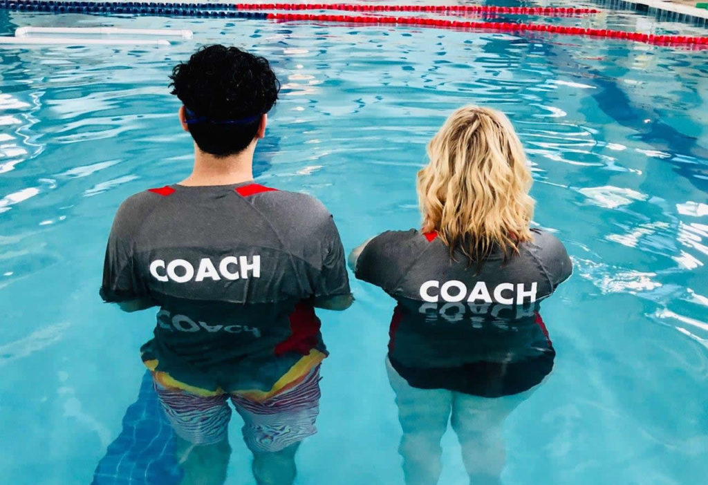 Two swim coaches standing in water